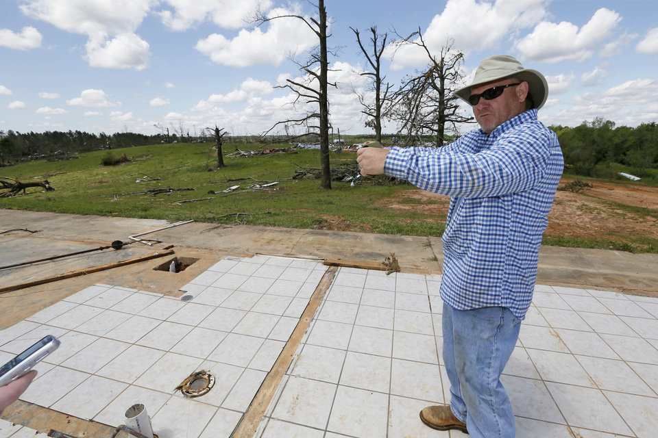 Photo - Terry Hartness, former owner of Hartness Farm, stands on the slab that was an office as he tells how the new owners held on to a full size refrigerator when a tornado hit the farm, a 12-chicken house operation that was leveled in Noxapater, Miss., Wednesday, April 30, 2014. The farm was sold on Friday and its new owners were at the farm when a tornado demolished the property and injured them. There were no chickens at the farm.  (AP Photo/Rogelio V. Solis)