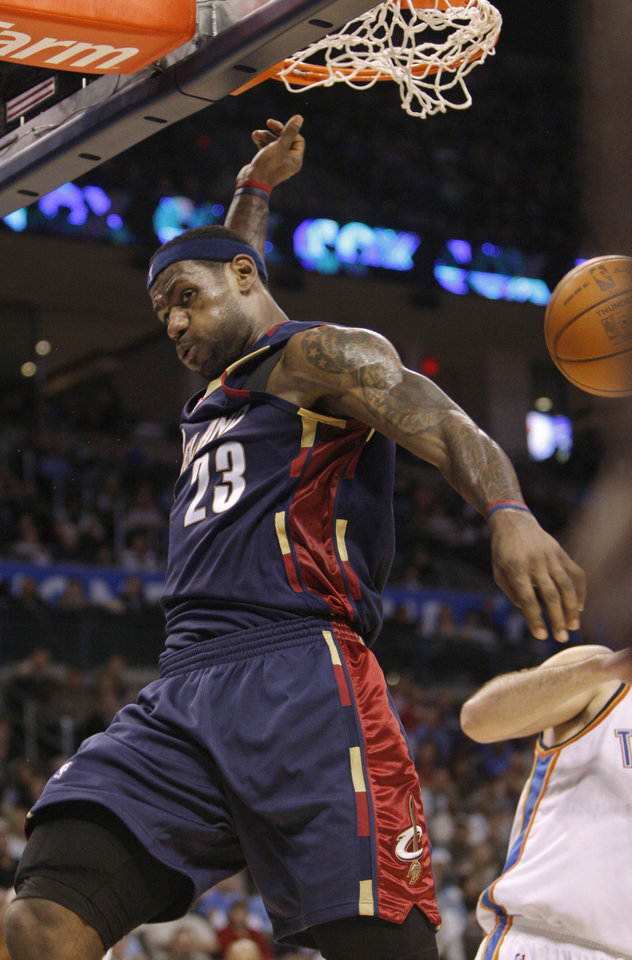 Photo - Cleveland Cavaliers forward LeBron James follows through on a dunk against the Oklahoma City Thunder in the second quarter of an NBA basketball game in Oklahoma City, Sunday, Dec. 13, 2009. (AP Photo/Sue Ogrocki) ORG XMIT: OKSO103