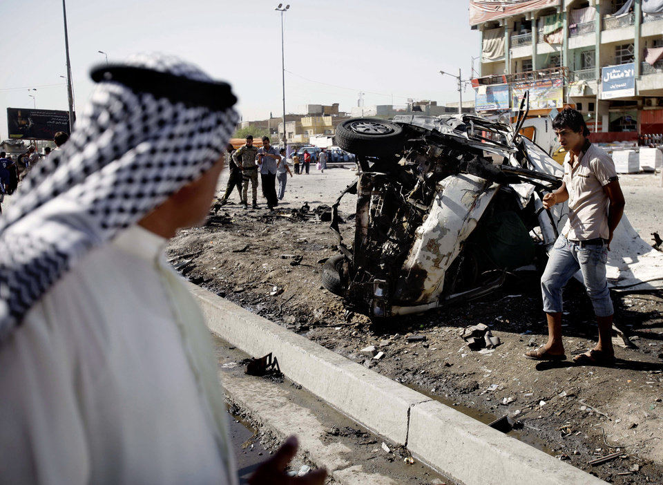 Iraqis inspect the aftermath of a car bomb attack, in the Shiite enclave of Sadr City, Baghdad, Iraq, Monday, July. 29, 2013. A wave of over a dozen car bombings hit central and southern Iraq during morning rush hour on Monday, officials said, killing scores in the latest coordinated attack by insurgents determined to undermine the government. (AP Photo/Karim Kadim)