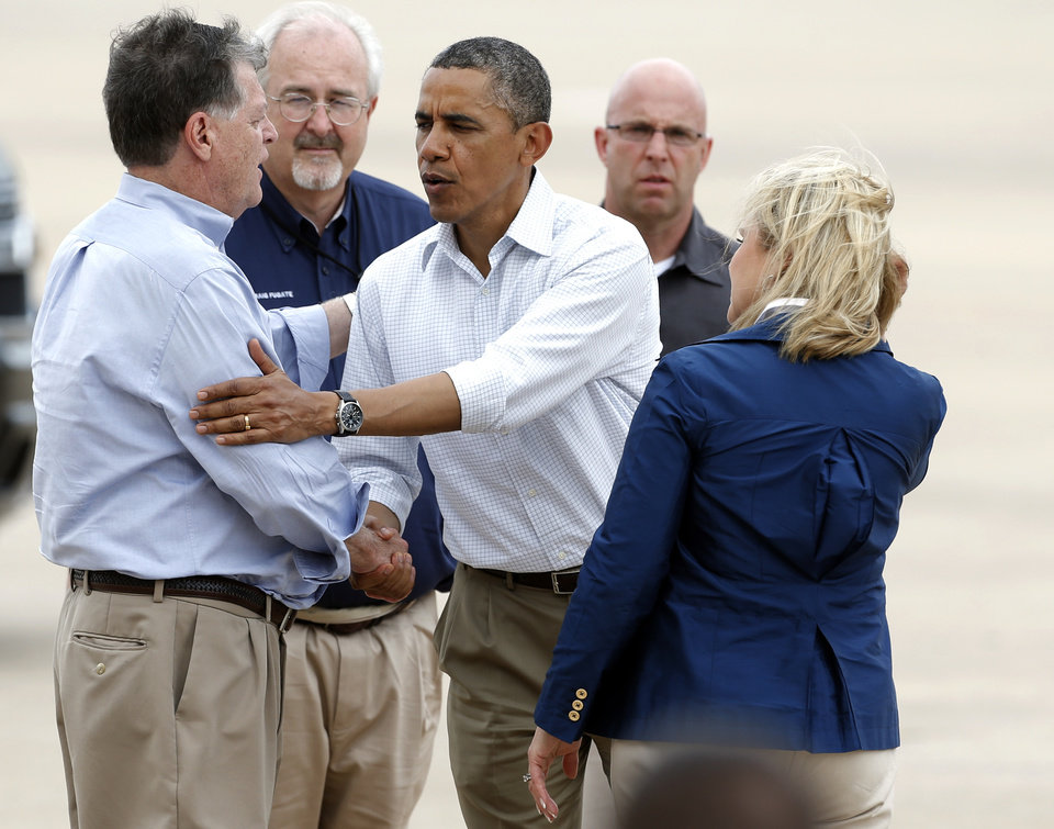 Photo - President Barack Obama shakes hands with U.S. Rep. Tom Cole as Gov. Mary Fallin looks on as leaves at Tinker Air Force base in Midwest City, Sunday, May 26, 2013. Obama was in town to visit areas damaged by the May 20 tornado. Photo by Sarah Phipps, The Oklahoman
