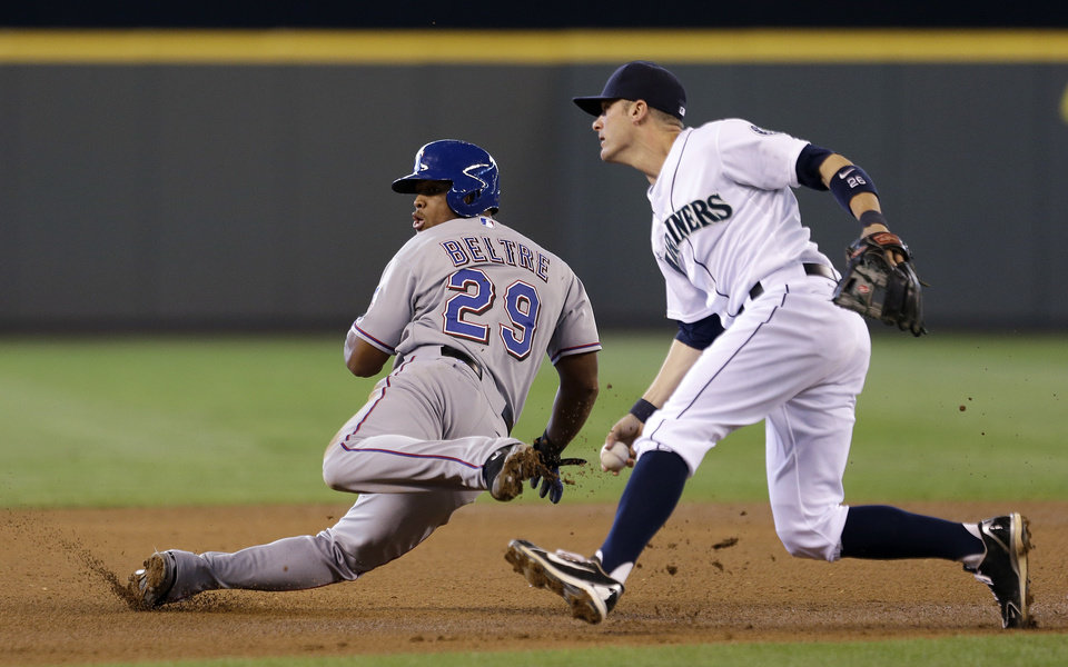 Texas Rangers' Adrian Beltre (29) tumbles after being tagged by Seattle Mariners shortstop Brendan Ryan in the seventh inning in the MLB American League baseball game Sunday, May 26, 2013, in Seattle. Beltre was out on the play. (AP Photo/Elaine Thompson)
