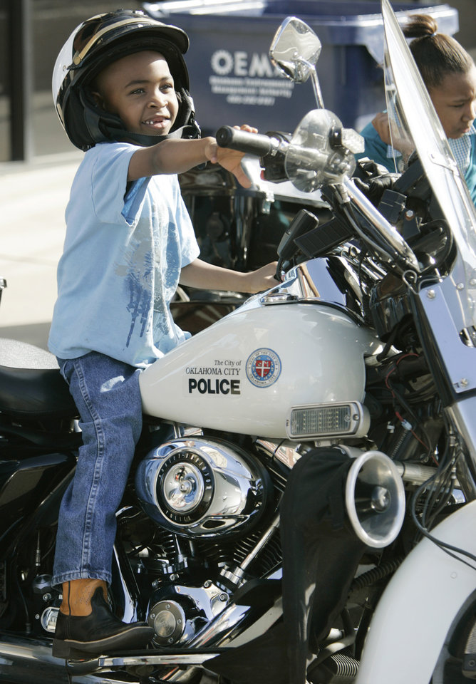 Photo - 6yr old Robert Taylor Jr. sits on an Oklahoma Police motorcycle before the start of the Martin Luther King Jr. Day Parade in Oklahoma City, Oklahoma January 18, 2010. Photo by Steve Gooch, The Oklahoman