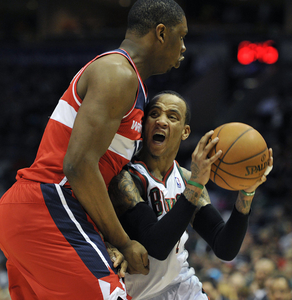 Washington Wizards' Kevin Seraphin, left, guards Milwaukee Bucks' Monta Ellis as he drives to the basket during the second half of an NBA basketball game Monday, Feb. 11, 2013, in Milwaukee. The Wizards defeated the Bucks 102-90. (AP Photo/Jim Prisching)