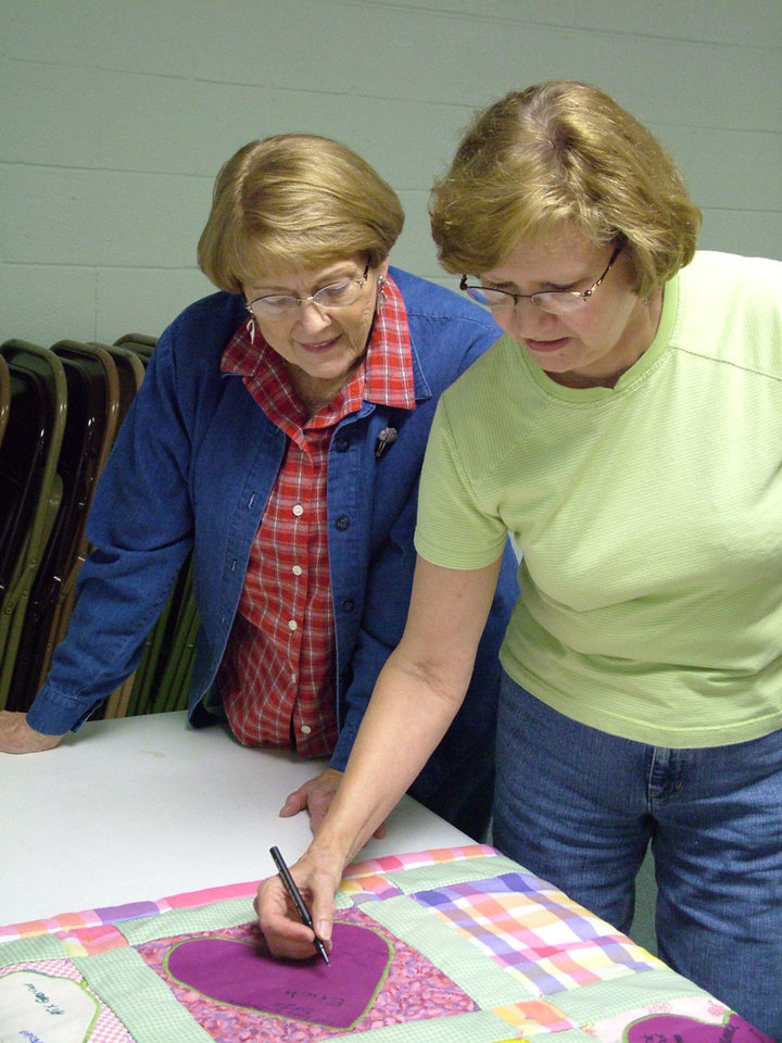 "Harrah residents Shirley Thompson and Doris Pettiet look to sign the ""Our Hearts Will Keep You Warm"" quilt that was especially made for former residents Sammi and Tim Ewing. The Ewings are now at Kadena AFB, Japan, but hope to make their home again in Harrah after their tour of duty in the Far East. All are members of Harrah United Methodist Church and the quilt was made by the church's Quilting Divas.<br/><b>Community Photo By:</b> Lin Archer<br/><b>Submitted By:</b> Lin,"