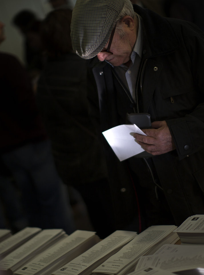 A voters choices his ballot paper to cast his vote in a polling station in Barcelona, Spain, on Sunday, Nov. 25, 2012. Voters in Catalonia begin casting their ballots in regional elections that could determine the future shape of Spain. If voters give the regional government strong support, its leader pledged to hold a referendum asking Catalans if they'd prefer to split from Spain and go it alone in the 27-member EU. (AP Photo/Emilio Morenatti)