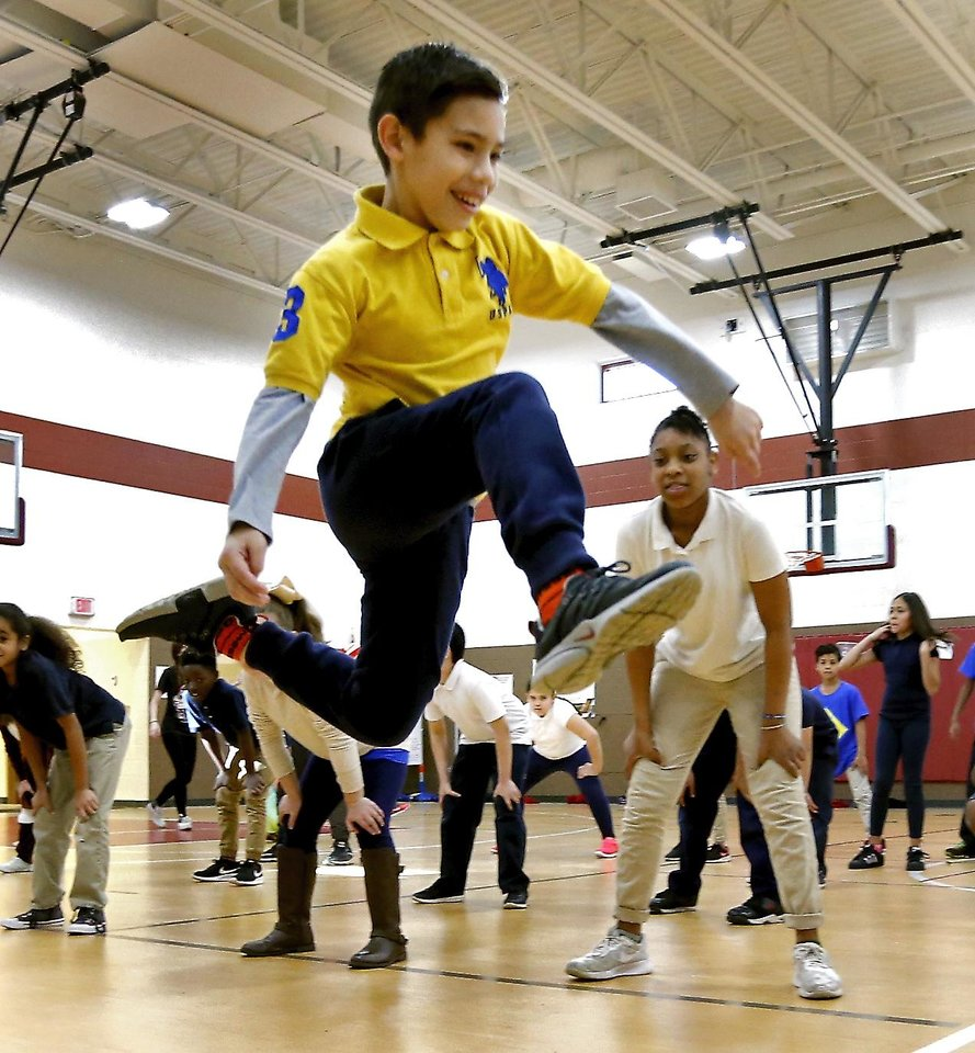 Photo -  Prairie Queen Elementary student Luis Fernandez leaps as a part of the Prairie Dance Theatre's elementary school dance program. [PHOTO BY STEVE SISNEY, THE OKLAHOMAN]