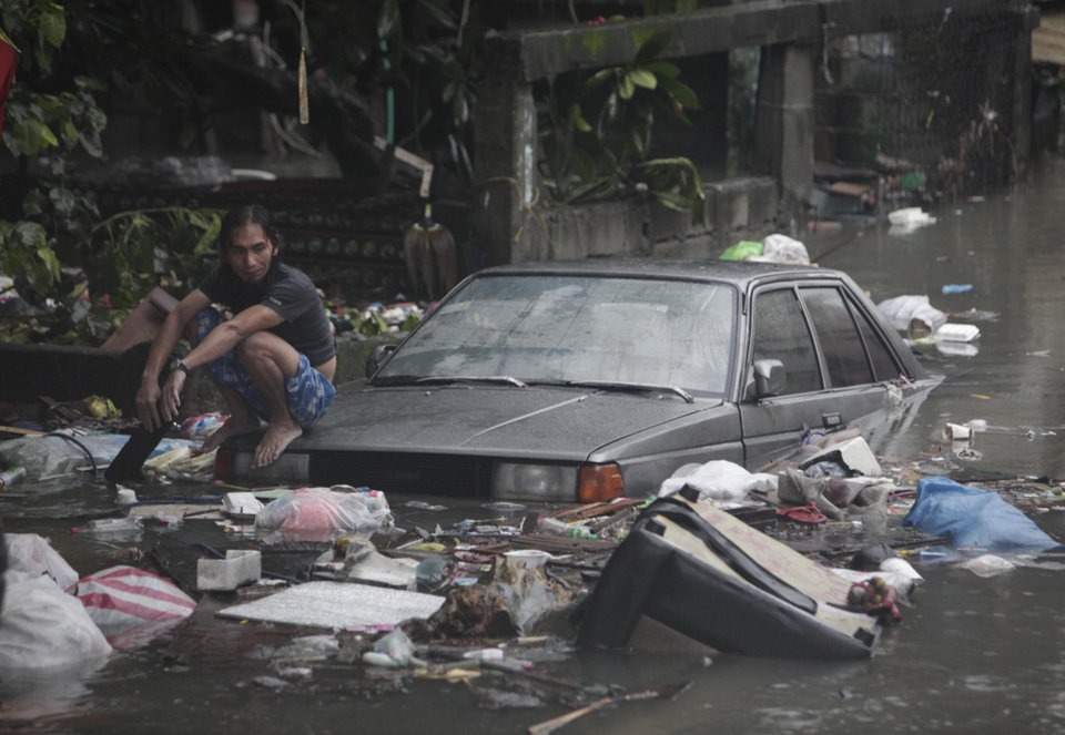 A man sits on the remains of a car along a flooded area in San Juan, east of Manila, Philippines, Wednesday Aug. 8, 2012. Widespread flooding battered a million others and paralyzed the Philippine capital began to ease Wednesday as cleanup and rescue efforts focused on a large number of distressed residents, some still marooned on their roofs. (AP Photo/John Javellana) ORG XMIT: XAF127