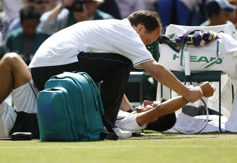 Photo - Novak Djokovic of Serbia receives treatment on his shoulder during the men's singles match against Gilles Simon of France at the All England Lawn Tennis Championships in Wimbledon, London, Friday, June 27, 2014. (AP Photo/Sang Tan)