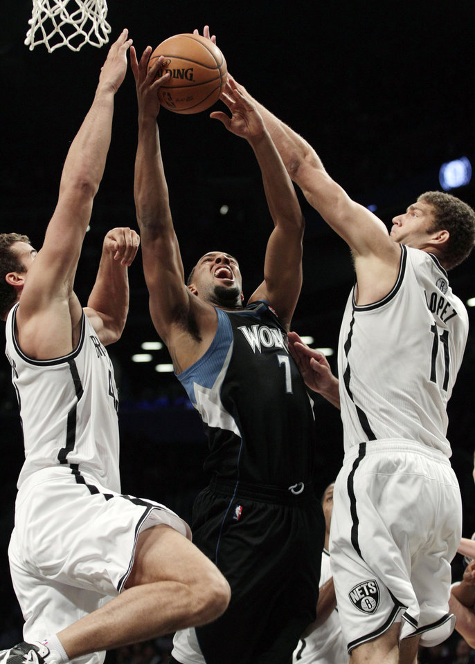 Photo -   Brooklyn Nets' Brook Lopez (11) and Kris Humphries (43) defend Minnesota Timberwolves' Derrick Williams (7) during the first half of an NBA basketball game, Monday, Nov. 5, 2012, in New York. (AP Photo/Frank Franklin II)