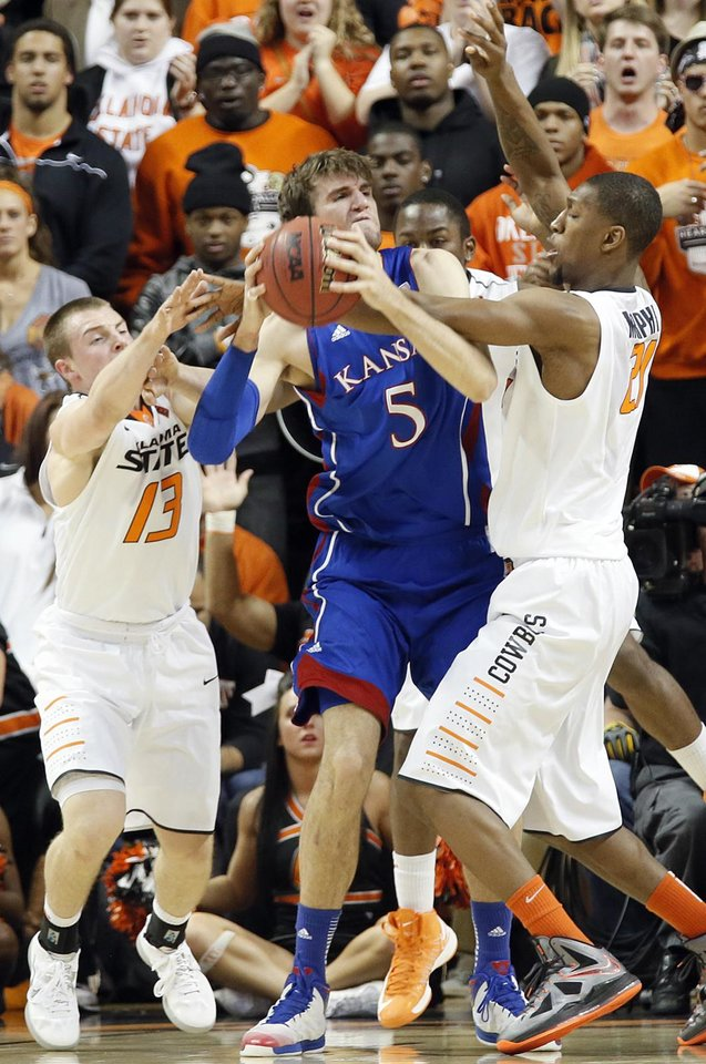 Photo - Oklahoma State 's Phil Forte (13) and Kamari Murphy (21) defend on Kansas' Jeff Withey (5) during the college basketball game between the Oklahoma State University Cowboys (OSU) and the University of Kanas Jayhawks (KU) at Gallagher-Iba Arena on Wednesday, Feb. 20, 2013, in Stillwater, Okla. Photo by Chris Landsberger, The Oklahoman