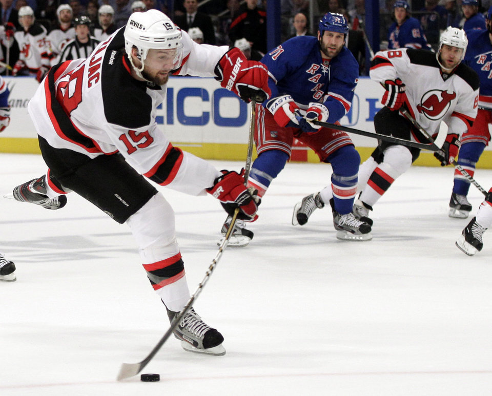 Photo -   New Jersey Devils' Travis Zajac, left, scores against the New York Rangers during the first period of Game 5 of an NHL hockey Stanley Cup Eastern Conference final playoff series, Wednesday, May 23, 2012, in New York. Rangers' Mike Rupp, center, and Devils' Dainius Zubrus, of Lithuania, right, watche the shot. (AP Photo/Frank Franklin II)