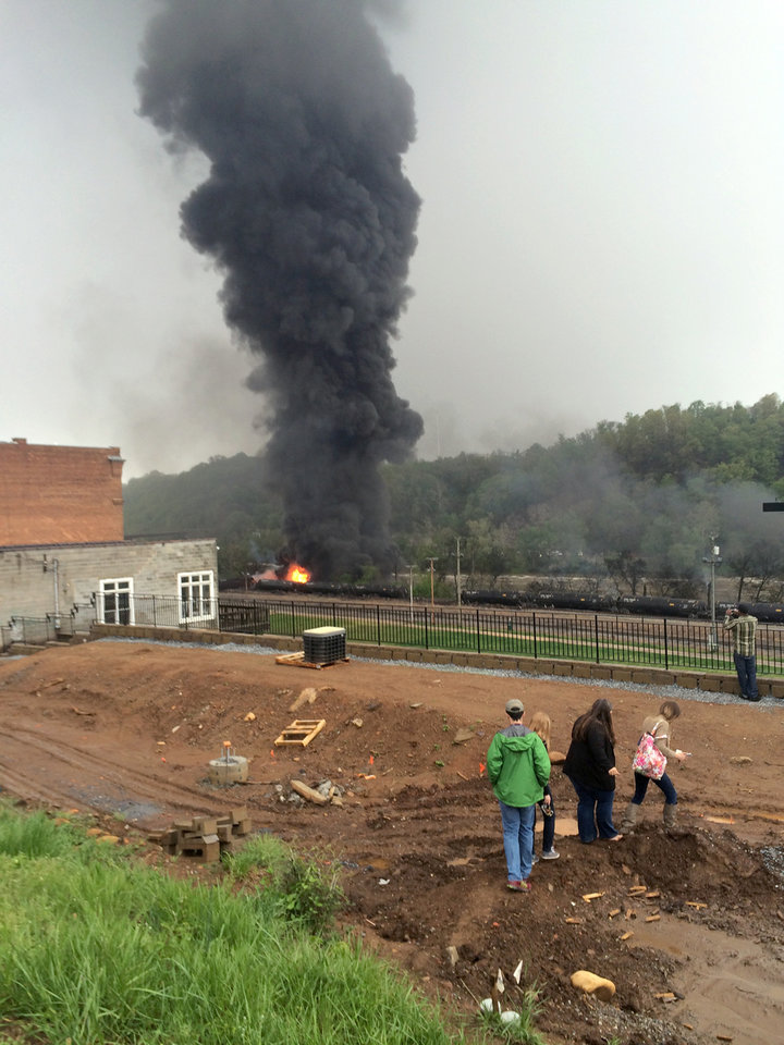 Photo - In this mobile phone photo provided Charles Peters, people look on as smoke rises after several CSX tanker cars carrying crude oil derailed on Wednesday, April 30, 2014, in Lynchburg, Va. Authorities evacuated numerous buildings Wednesday after the derailment. (AP Photo/Charles Peters) MANDATORY CREDIT