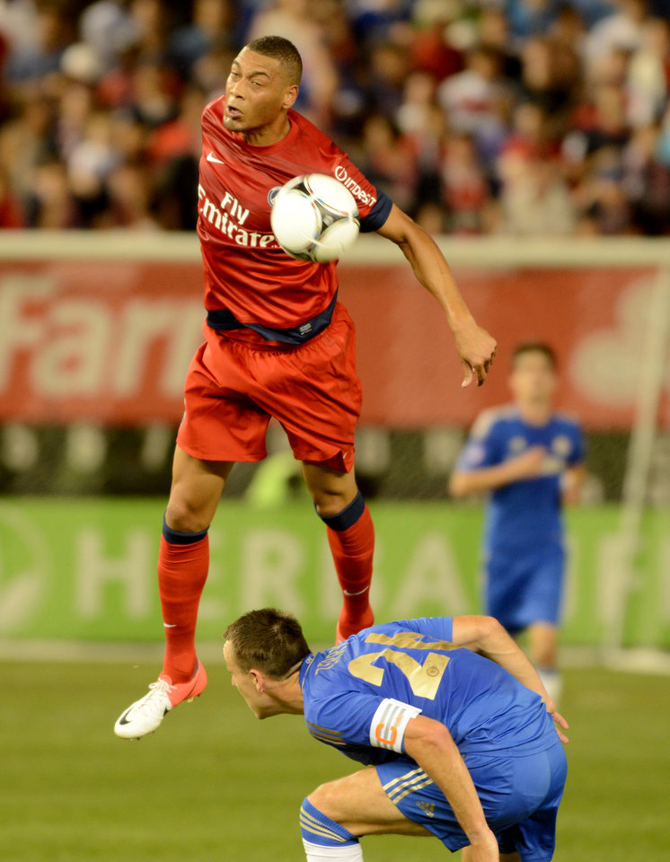 Photo -   Paris Saint-Germain's Guillaume Hoarau, top, heads the ball past Chelsea FC's John Terry during the second half of their soccer match at Yankee Stadium in New York, Sunday, July 22, 2012. The game ended in a 1-1 draw. (AP Photo/Henny Ray Abrams)
