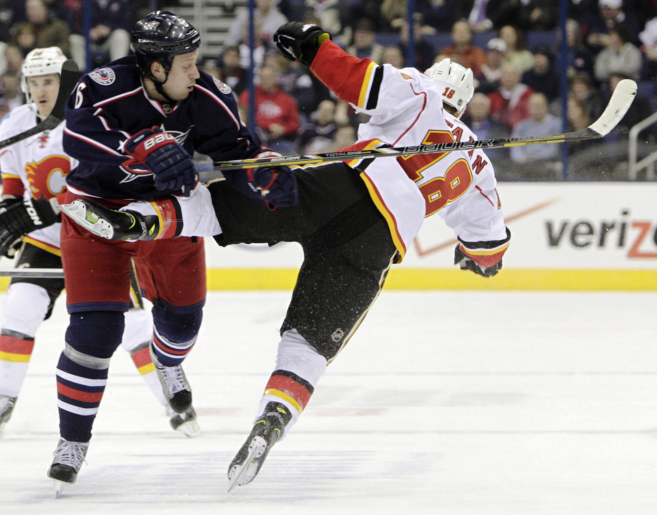 Columbus Blue Jackets' Nikita Nikitin, left, of Russia, knocks Calgary Flames' Matt Stajan to the ice during during the first period of an NHL hockey game, Thursday, Feb. 7, 2013, in Columbus, Ohio. (AP Photo/Jay LaPrete)