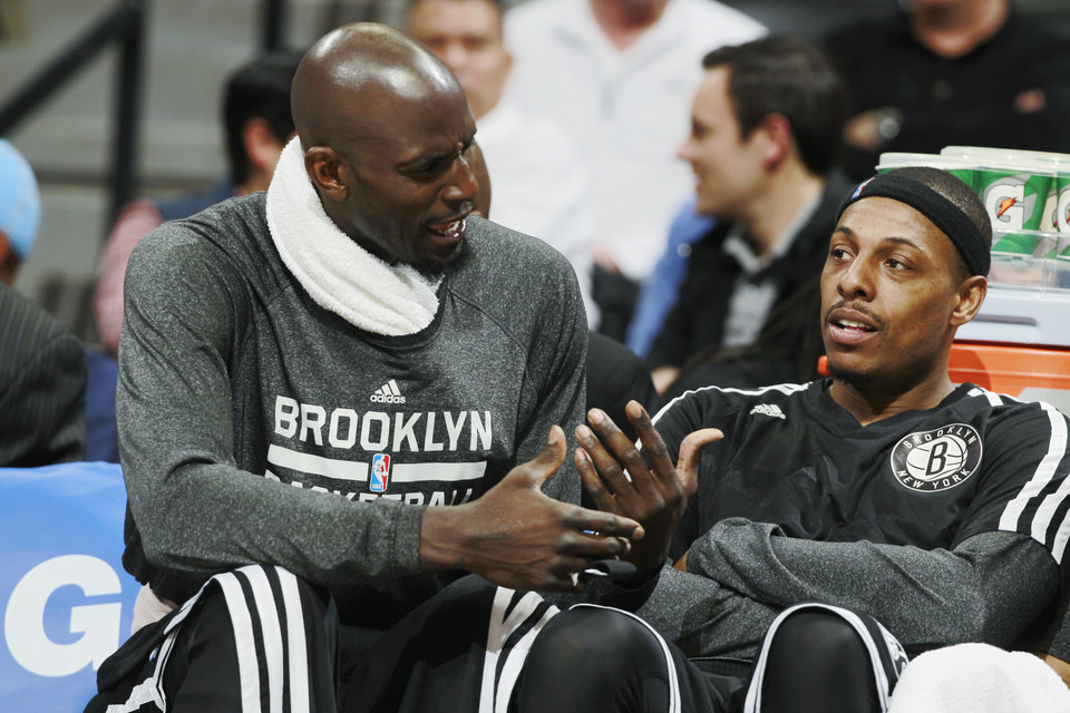 Photo - Brooklyn Nets forwards Kevin Garnett, left, and Paul Pierce confer while on the bench as the Nets face the Denver Nuggets in the third quarter of the Nets' 112-89 victory in an NBA basketball game in Denver on Thursday, Feb. 27, 2014. (AP Photo/David Zalubowski)