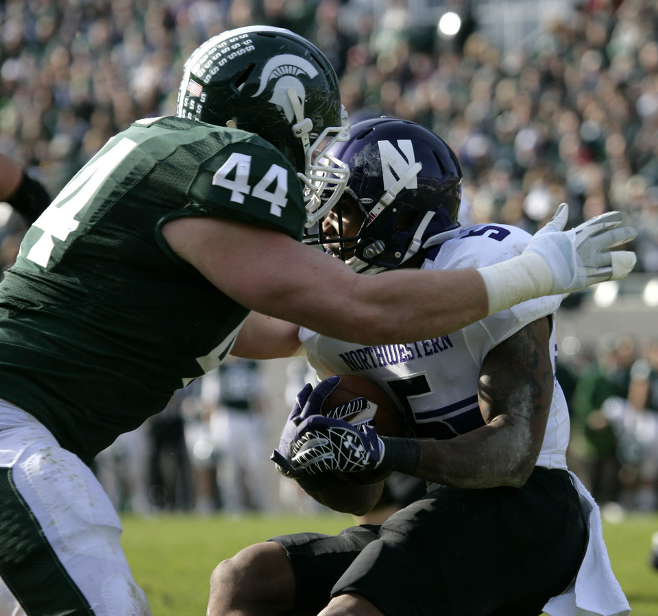 Photo -   Northwestern's Venric Mark, right, is stopped by Michigan State's Marcus Rush during the first quarter of an NCAA college football game, Saturday, Nov. 17, 2012, in East Lansing, Mich. Northwestern won 23-20. (AP Photo/Al Goldis)