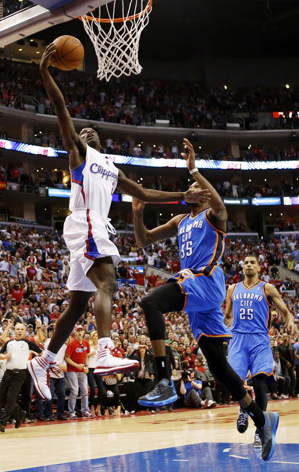 Photo - Los Angeles' Darren Collison (2) lays up the ball past Oklahoma City's Kevin Durant (35) and Thabo Sefolosha (25) in the last minute of the fourth quarter during Game 4 of the Western Conference semifinals in the NBA playoffs between the Oklahoma City Thunder and the Los Angeles Clippers at the Staples Center in Los Angeles, Sunday, May 11, 2014. The Clippers won 101-99. Photo by Nate Billings, The Oklahoman