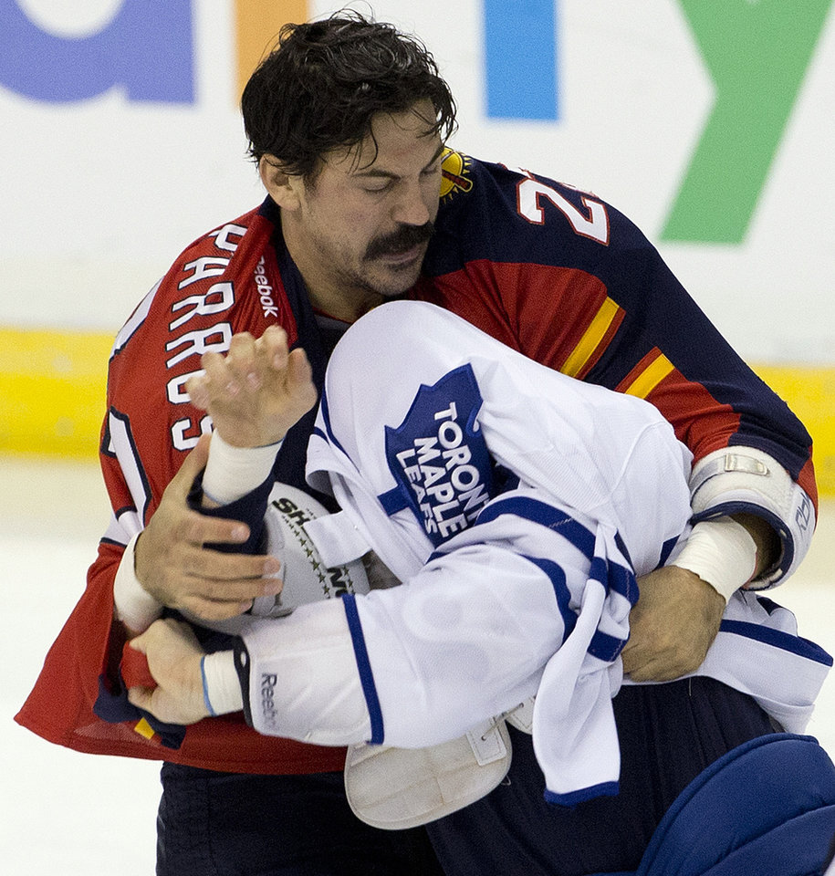 Photo - Florida Panthers' George Parros, rear,  and Toronto Maple Leafs' Colton Orr fight during the first period of an NHL hockey game in Sunrise, Fla., Monday, Feb. 18, 2013.  (AP Photo/J Pat Carter)