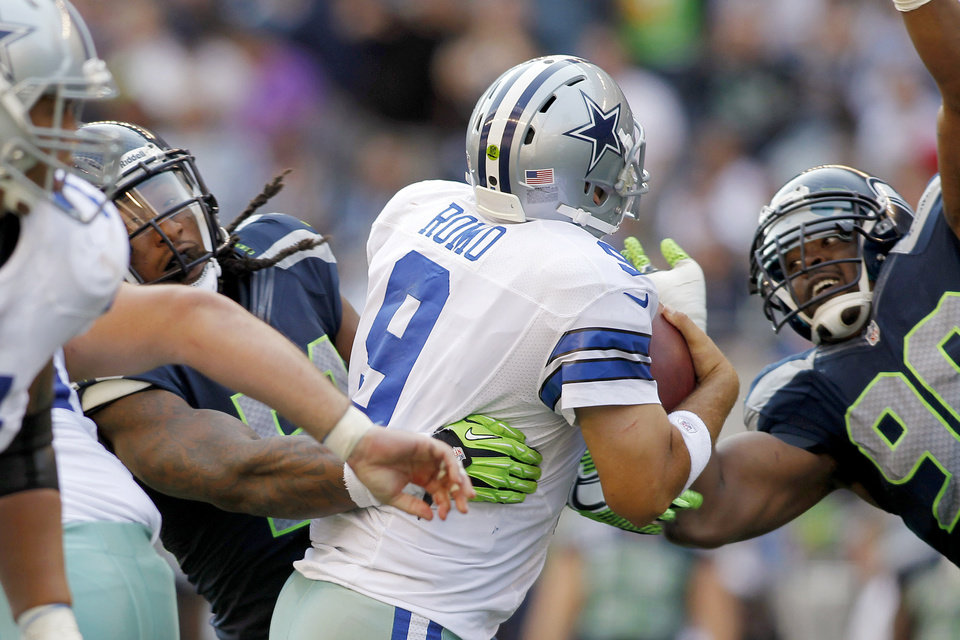 Photo -   Seattle Seahawks' Greg Scruggs, left, and Jason Jones (90) move in to sack Dallas Cowboys quarterback Tony Romo in the second half of an NFL football game, Sunday, Sept. 16, 2012, in Seattle. (AP Photo/John Froschauer)