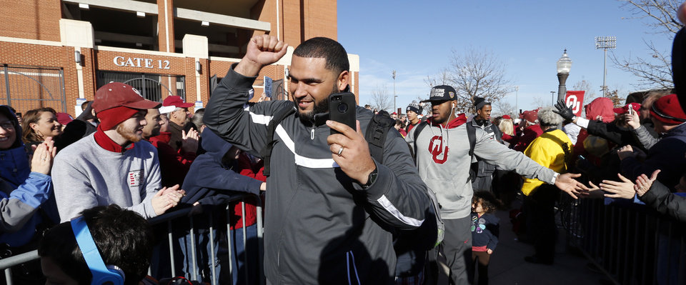 Photo - Members of the Sooner team are greeted by several hundred fans gathered to welcome the University of Oklahoma Sooner (OU) football team as they return victorious from the Sugar Bowl on Friday, Jan. 3, 2014 in Norman, Okla.  Photo by Steve Sisney, The Oklahoman