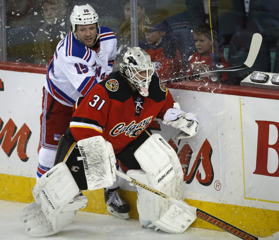 Photo - New York Rangers' Derek Dorsett, left, tries to get past Calgary Flames goalie Karri Ramo, from Finland, dduring the second period of an NHL hockey game in Calgary, Alberta, Friday, March 28, 2014. (AP Photo/The Canadian Press, Jeff McIntosh)