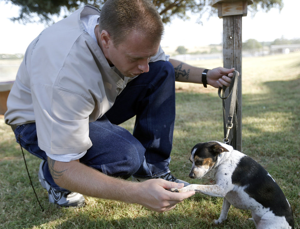 Inmate Luke Sinclair shakes paws with Oreo at the Lexington Assessment and Reception Center, Friday, July 11,  2013, in Lexington, Okla. Photo by Sarah Phipps, The Oklahoman
