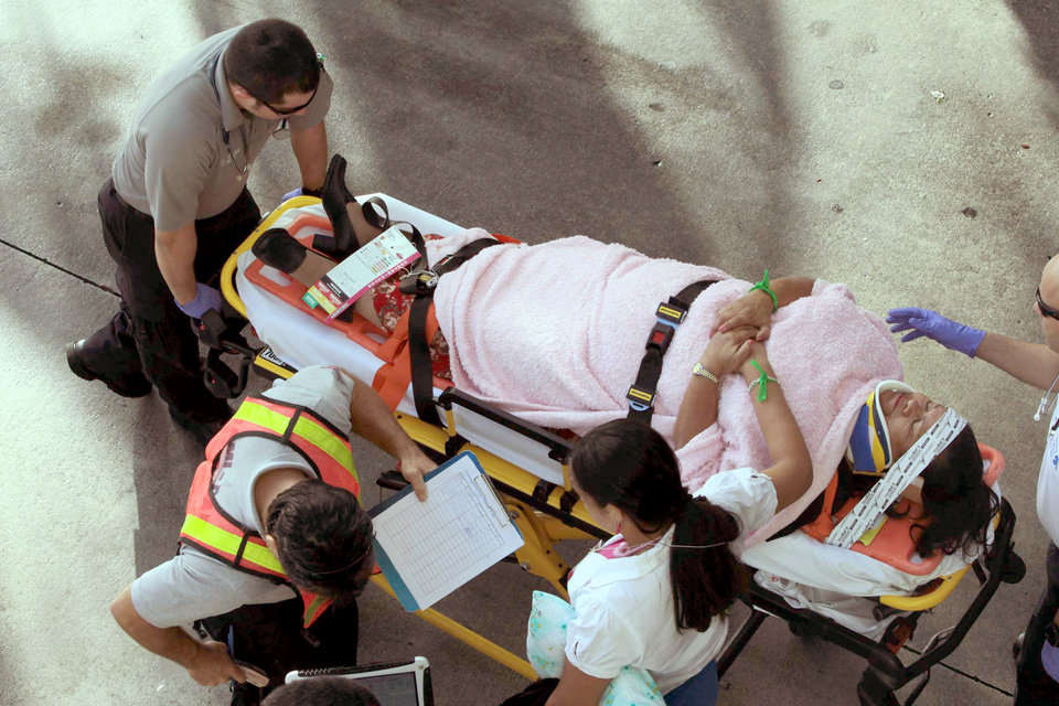 Photo - Emergency personnel attend to injured passengers after a bus accident at Miami International Airport on Saturday, Dec. 1, 2012 in Miami. Officials say a bus has hit an overpass, killing at least one person and injuring more than two-dozen people on board. Airport spokesman Greg Chin says the large, white bus hit the overpass going into the airport's arrivals section on Saturday morning. The bus was going about 20 mph when it clipped the roof entrance. (AP Photo/El Nuevo Herald, Roberto Koltun)