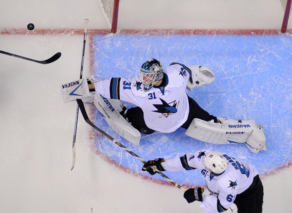 Photo - San Jose Sharks goalie Antti Niemi, top, of Finland, deflects a shot as defenseman Justin Braun reaches in during the first period in Game 3 of an NHL hockey first-round playoff series  against the Los Angeles Kings, Tuesday, April 22, 2014, in Los Angeles. (AP Photo/Mark J. Terrill)