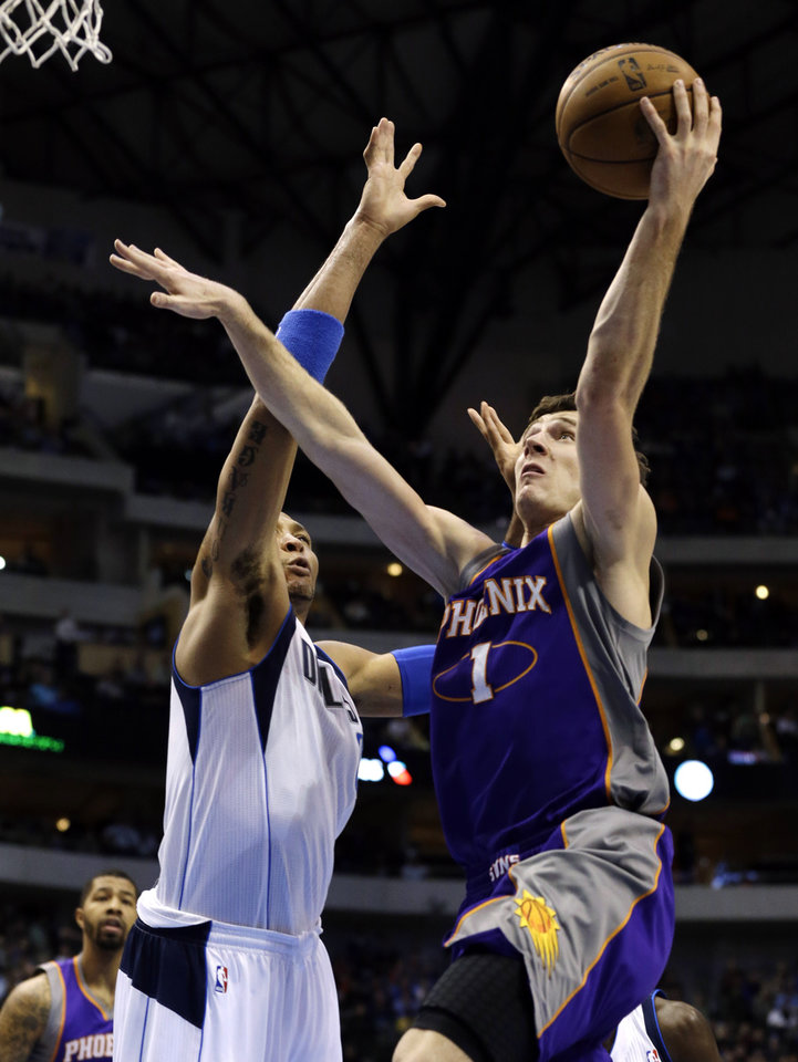 Photo - Dallas Mavericks' Shawn Marion (0) defends as Phoenix Suns' Goran Dragic (1), of Slovenia, shoots in the first half of an NBA basketball game, Sunday, Jan. 27, 2013, in Dallas. (AP Photo/Tony Gutierrez)