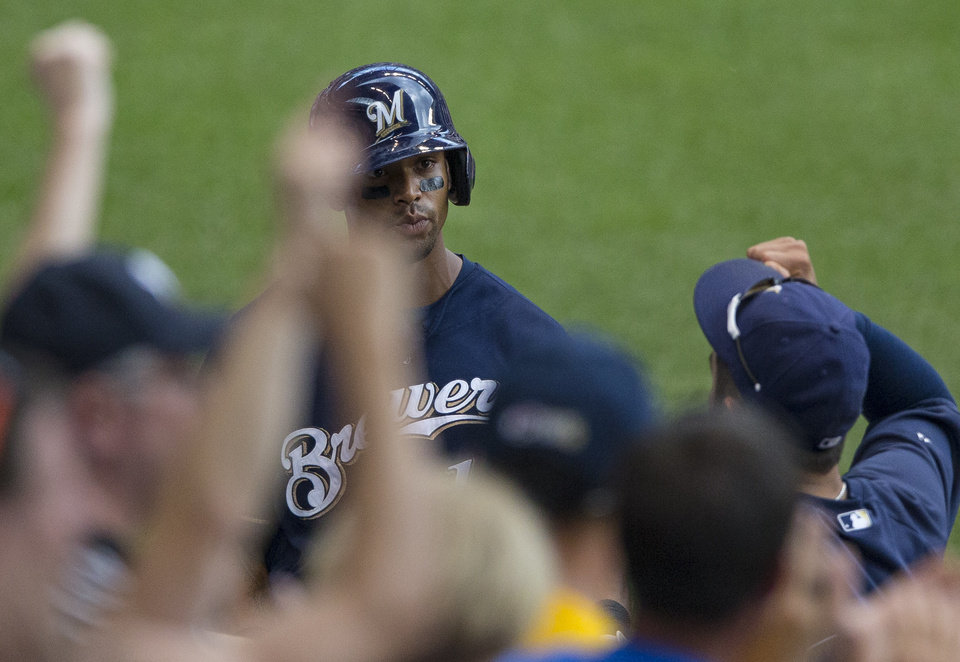 Photo - Milwaukee Brewers' Khris Davis is cheered on by fans and teammates after his solo home run against the St. Louis Cardinals during the fifth  inning of a baseball game Sunday, July 13, 2014, in Milwaukee. (AP Photo/Tom Lynn)
