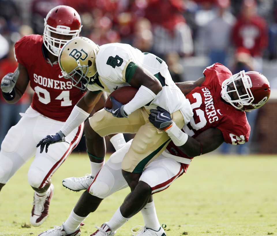 Photo - Lanear Sampson is brought down by Keenan Clayton (22) after a short pass gain during the first half of the college football game between The University of Oklahoma Sooners (OU) and the Baylor Bears at the Gaylord Family-Oklahoma Memeorial Stadium on Saturday, Oct. 10, 2009, in Norman, Okla.