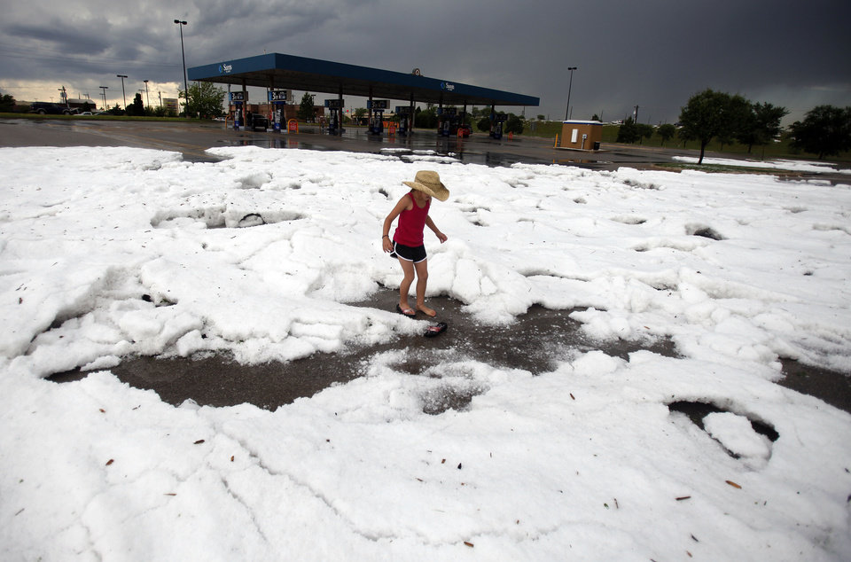 Riley Thompson, 8, of Edmond, Okla., plays on mound of hailstones in the Sam's Club parking lot on Pennsylvania Avenue near Memorial Road, Sunday, May 16, 2010 in Oklahoma City. Photo by Sarah Phipps, The Oklahoman