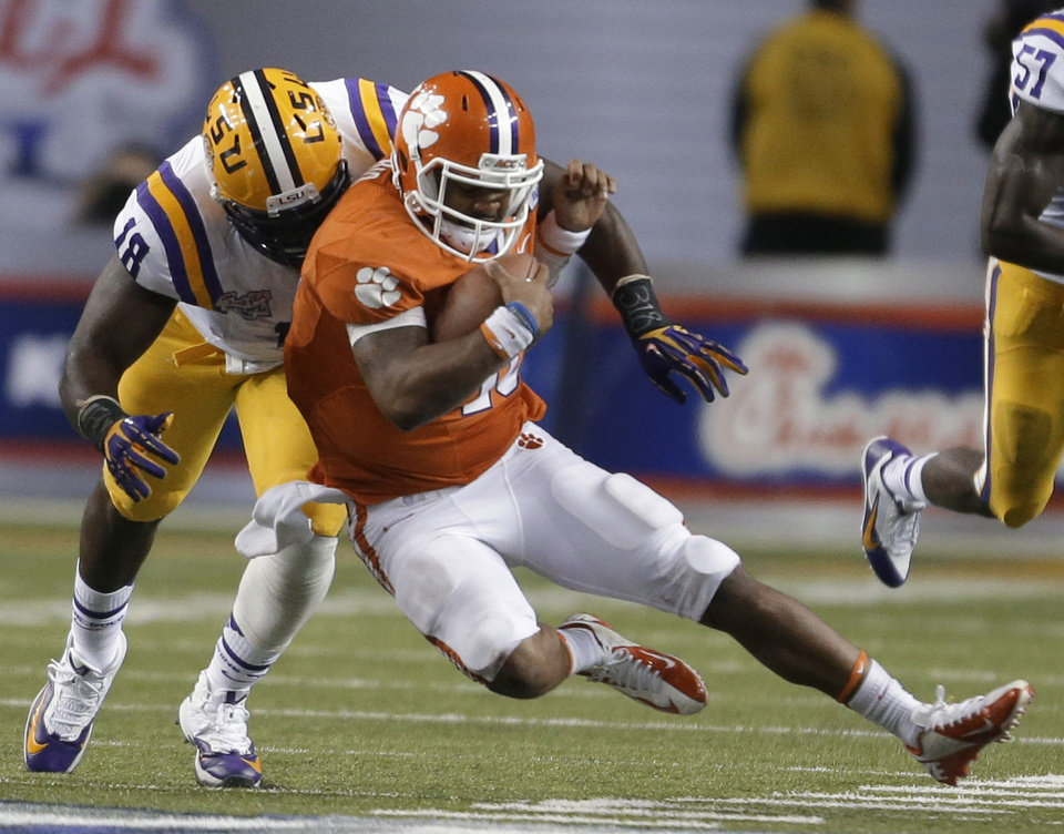Photo - Clemson quarterback Tajh Boyd (10) is tackled by LSU defensive tackle Bennie Logan (18) during the second half of the Chick-fil-A Bowl NCAA college football game, Monday, Dec. 31, 2012, in Atlanta. (AP Photo/David Goldman)