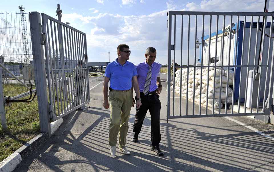 Photo - The head of the OSCE (Organization for Security and Cooperation in Europe) mission, acting Chief Observer Paul Picard, right, walks with Vadim Artyomov, deputy governor of Rostov region, left, while visiting the Gukovo border checkpoint at Russia-Ukraine border in a small town of Gukovo, 120 kms (75 miles ) from Rostov-on-Don, Russia, Wednesday, July 30, 2014. The mission will be based in the city of Kamensk-Shakhtinskiy, in the Rostov-on-Don region. (AP Photo/Sergei Pivovarov)