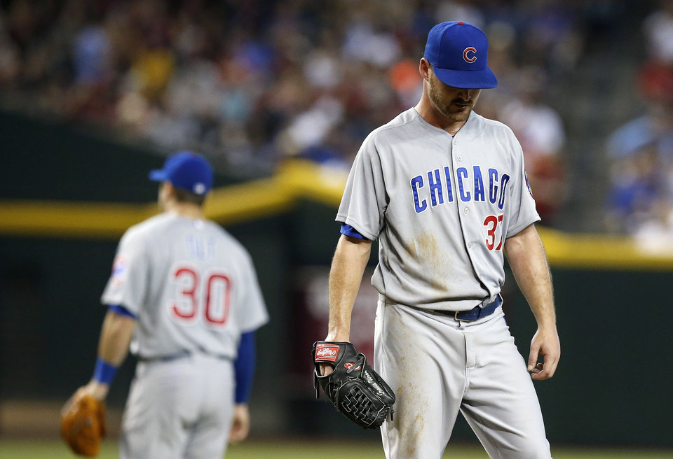 Photo - Chicago Cubs' Travis Wood, right, pauses at the pitcher's mound after getting a visit from teammates, including Mike Olt (30), as Wood gives up four runs during the fifth inning of a baseball game against the Arizona Diamondbacks on Saturday, July 19, 2014, in Phoenix. (AP Photo/Ross D. Franklin)