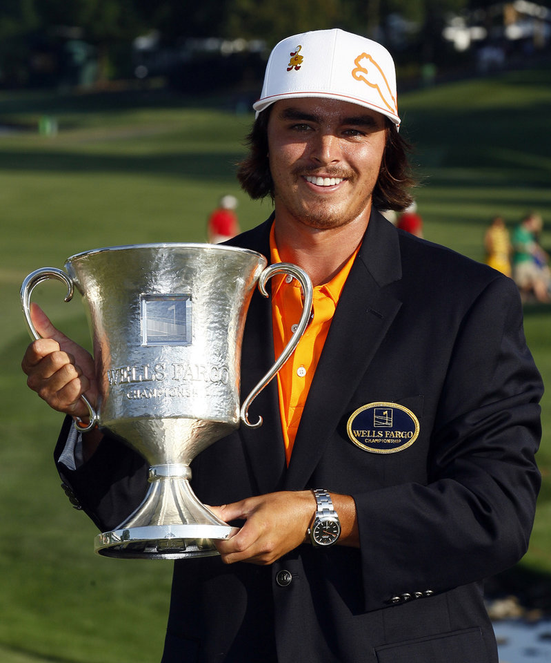 Photo -   Rickie Fowler holds the trophy after winning the Wells Fargo Championship golf tournament at Quail Hollow Club in Charlotte, N.C., Sunday, May 6, 2012. (AP Photo/Gerry Broome)