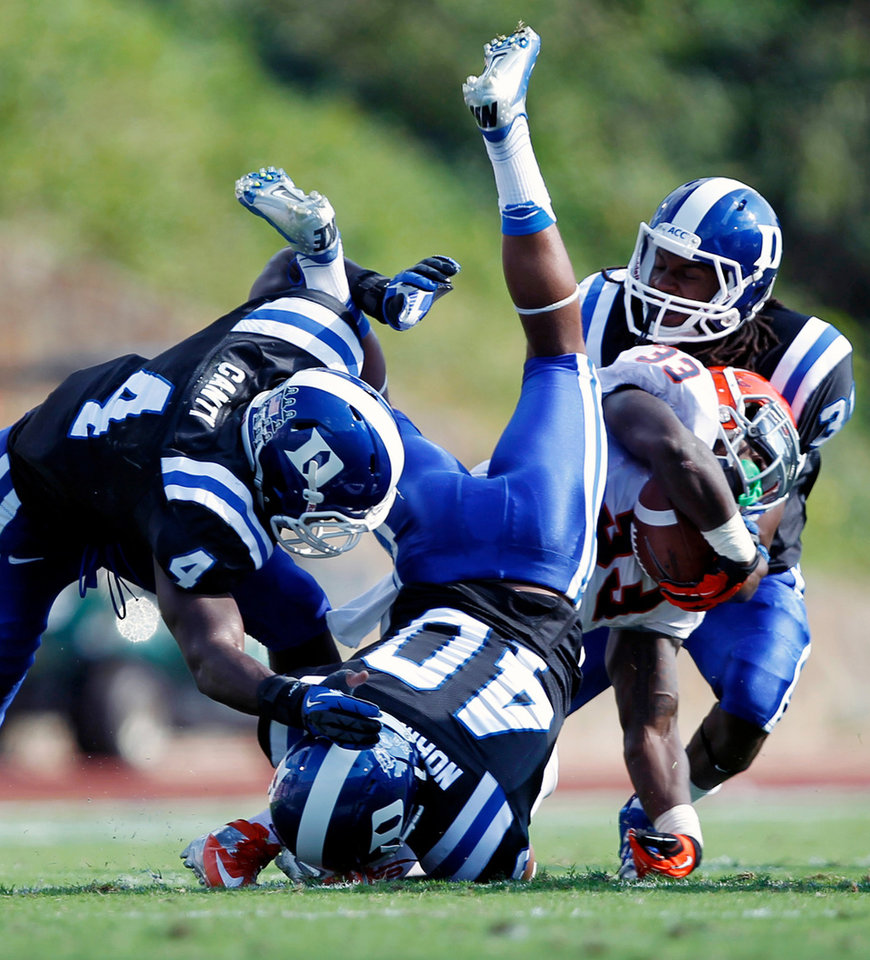 Duke defenders Walt Canty (4), Dwayne Norman (40) and Tony Foster (31) take down Virginia running back Perry Jones (33) during the second quarter of an ACC college football game in Durham, N.C., Saturday, Oct. 6, 2012. (AP Photo/The News & Observer, Chris Seward)