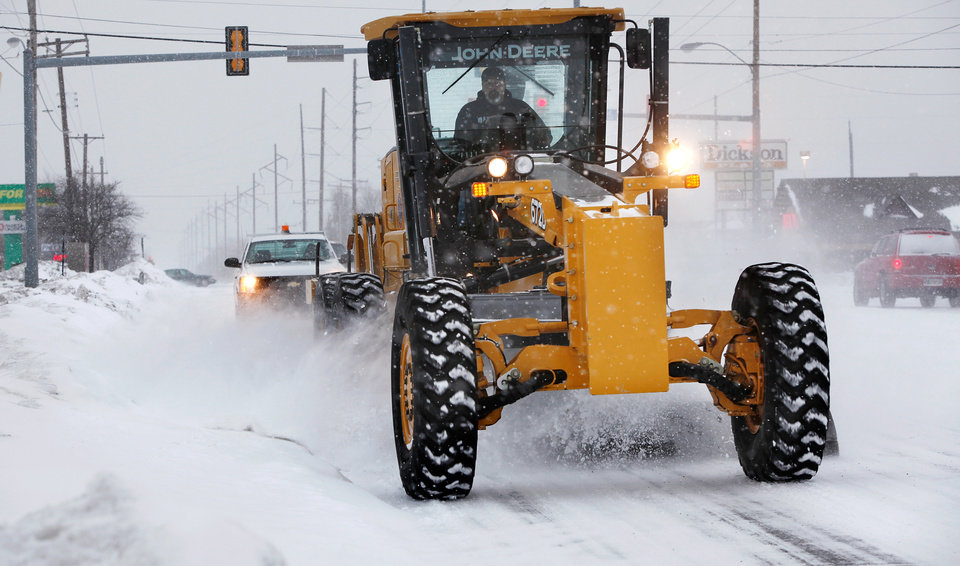 Photo - A city road grader plows snow from westbound lanes of SE 15th Street in Midwest City. A second winter storm in a week dumped about 6 inches of snow in the Oklahoma City area Tuesday morning, Feb. 9, 2011.   Photo by Jim Beckel, The Oklahoman
