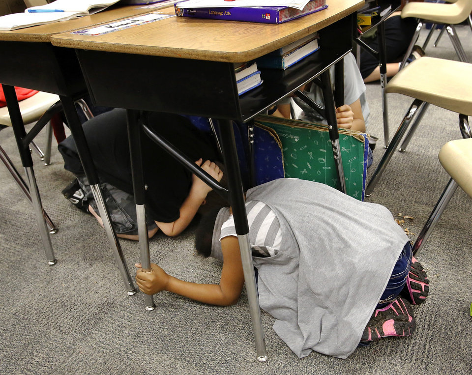 """Students take cover under their desks in Melinda Jordan's fourth grade classroom.  Cleveland Bailey Elementary School students participated in the """"Drop, Cover and Hold-on"""" multi-state earthquake drill at the Midwest City school Wednesday,  Feb. 7,  2013.    Photo by Jim Beckel, The Oklahoman"""