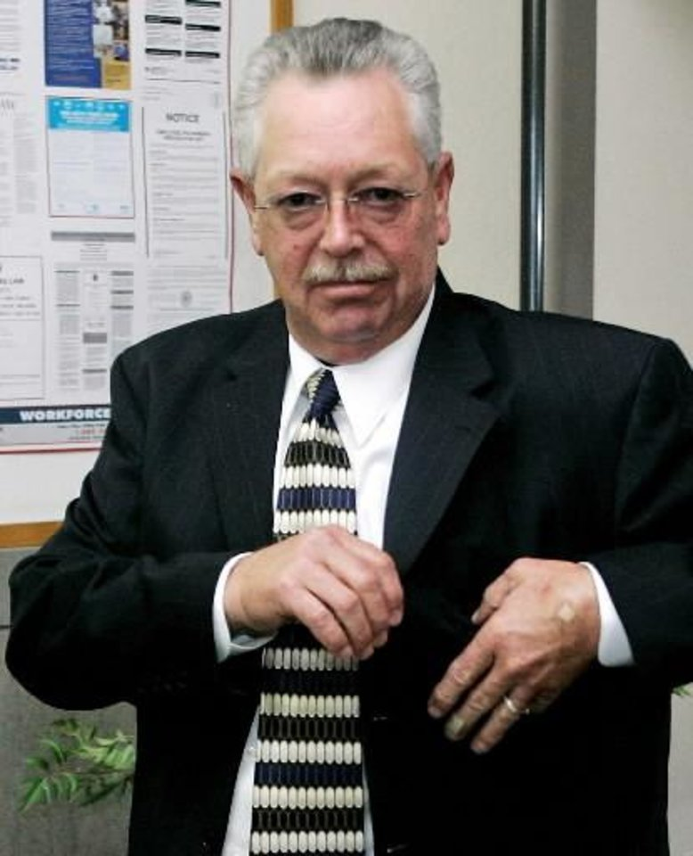 Photo - In this Aug. 12, 2008 file photo former Custer County Sheriff Mike Burgess, goes through security as he enters the courthouse in Arapaho. AP Photo