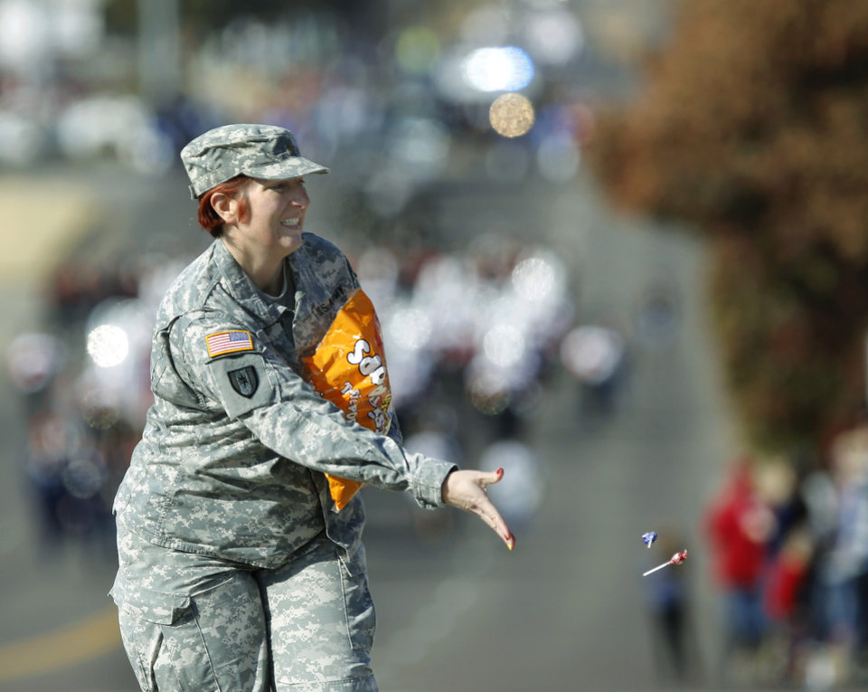 Photo - An officer in the US Army throws candy to children along the route of the Midwest City Veteran's Day Parade on Friday, Nov. 10, 2017. Photo by Jim Beckel, The Oklahoman