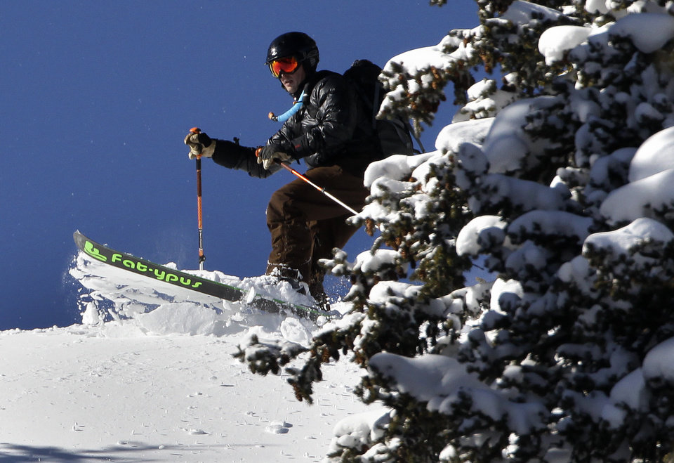 Photo - A man skis though deep powder from a storm a day earlier, after hiking up a public mountainside atop Berthoud Pass, near Winter Park, Colo., Thursday Dec. 20, 2012. The fresh snow, with more expected before Christmas, has left much of Colorado ski-country replenished after a relatively warm and dry Fall. (AP Photo/Brennan Linsley)