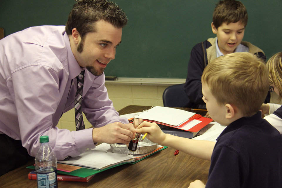 Daniel Buckmaster, the Oklahoma City School District's Teacher of the Year, works with his science students at Belle Isle Enterprise Middle School.   PROVIDED PHOTO BY COLIN STRICKLAND, THE FOUNDATION FOR OKLAHOMA CITY PUBLIC SCHOOLS  <strong></strong>