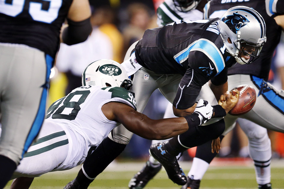 Photo -   New York Jets defensive end Quinton Coples (98) knocks the ball away from Carolina Panthers quarterback Cam Newton (1) during the first half of a preseason NFL football game, Sunday, Aug. 26, 2012, in East Rutherford, N.J. (AP Photo/Julio Cortez)