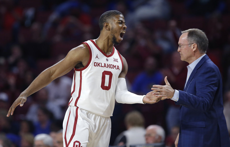 Photo - Oklahoma's Christian James (0) celebrates a 3-point basket with head coach Lon Kruger during the men's college basketball game between the University of Oklahoma and Kansas at the Lloyd Noble Center in Norman, Okla., Tuesday, March 5, 2019. Photo by Sarah Phipps, The Oklahoman