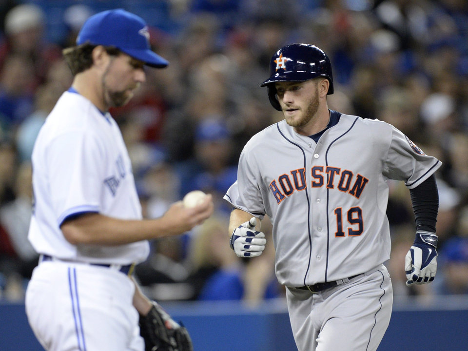 Photo - Houston Astros' Robbie Grossman rounds the bases after his two -un home  run as Toronto Blue Jays pitcher R.A. Dickey makes his way back to the mound during the fifth inning of baseball game in Toronto on Thursday, April 10, 2014. (AP Photo/The Canadian Press, Frank Gunn)
