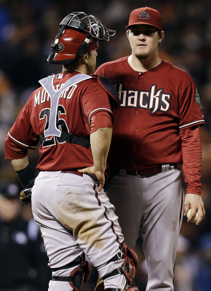 Photo -   Arizona Diamondbacks starting pitcher Wade Miley, right, gets a visit to the mound from catcher Miguel Montero after Miley loaded the bases against the San Francisco Giants during the fourth inning of a baseball game, Wednesday, Sept. 26, 2012, in San Francisco. (AP Photo/Marcio Jose Sanchez)