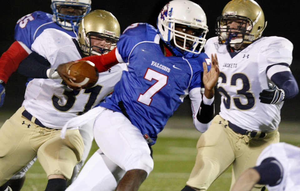 Photo - Millwood's Kevonte Richardson (7) gets past Kingfisher's Rhett Blundell (31) and Joe Gaither (63) during the Class 2A State semifinal football game between Millwood High School and Kingfisher High School on Saturday, Dec. 5, 2009, in Yukon, Okla. 