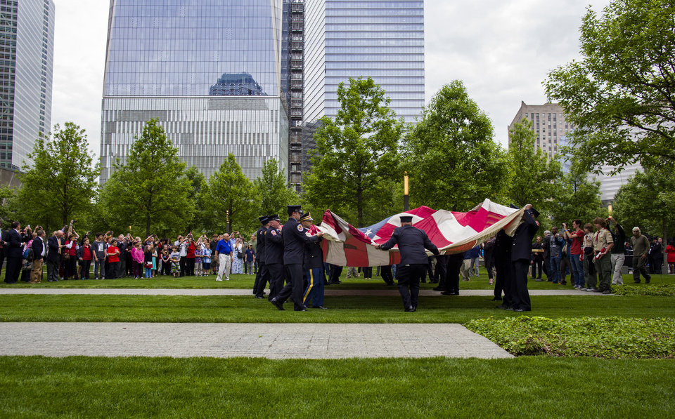 Photo - The National 9/11 Flag is unfurled during a ceremony at the 9/11 Memorial in New York Wednesday, May 21, 2014.  The ceremony Wednesday marked the opening of the National September 11 Memorial Museum. After the flag was refolded, firefighters marched it into the museum. The flag was flying from a building near the World Trade Center on Sept. 11, 2001. It was later found shredded in the debris of ground zero.  (AP Photo/Craig Ruttle)