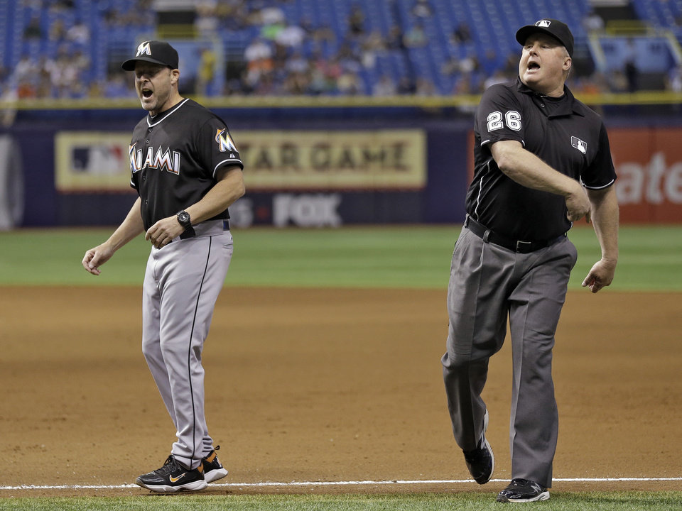 Photo - First base umpire Bill Miller, right, ejects Miami Marlins manager Mike Redmond after Redmond argued that a double by Tampa Bay Rays' Desmond Jennings was foul during the seventh inning of an interleague baseball game Thursday, June 5, 2014, in St. Petersburg, Fla. The play was not reviewable. (AP Photo/Chris O'Meara)